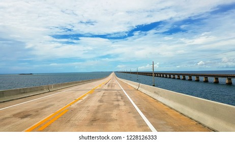 Travel in Florida by car, beautiful view of long Overseas Highway with cars, ocean water of Gulf of Mexico and power pylons on both sides of the road, old Overseas Railroad on the right side