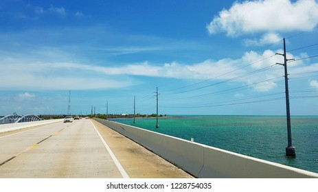 Travel in Florida by car, beautiful view of long Overseas Highway with cars, blue ocean water of Gulf of Mexico and power pylons on both sides of the road, island with tropical plants in the distance