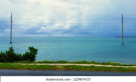 Travel in Florida Keys by car,  blue ocean water with reefs of Gulf of Mexico, view from Overseas highway to horizon, power pylon standing in water, cloudy sky