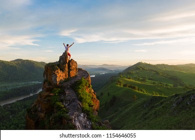 Travel, freedom leadership and real life concept - man standing on top of cliff in summer beauty sunset in Altai mountains