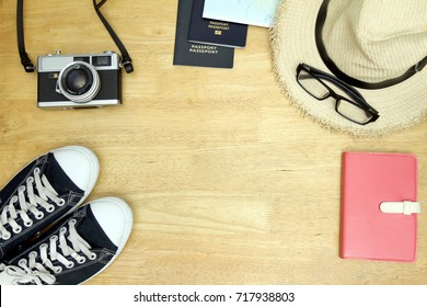 Travel gadgets such as passport, map, notebook, sneaker, camera, hat, glasses. Top view with Wood background