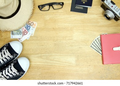Travel gadgets such as passport, notebook, camera, hat, sneaker, glasses, foreign money. Collect money for travel. Top view with Wood background