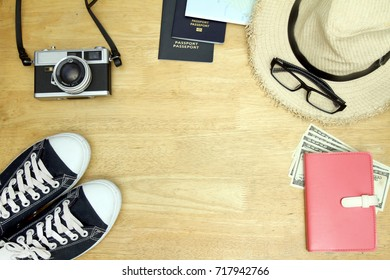 Travel gadgets such as passport, smart phone, ear pug, notebook, camera, hat, sneaker, glasses. Collect money for travel. Top view with Wood background