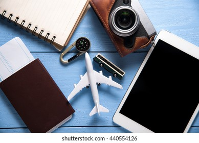 Travel gear and tablet on blue wooden background. Travel concept, top view