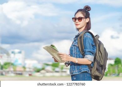 Travel Girl with backpack holding map.