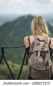 travel girl with backpack looking out at bokeh view