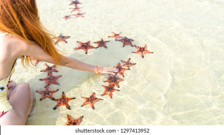 Travel girl in bikini with starfishes,making a heart for Valentines Day in honeymoon in Phu Quoc island with clear water and white sand beach