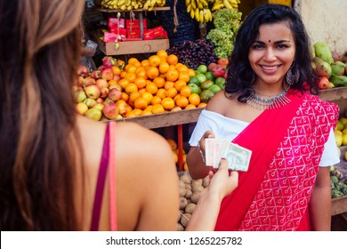 travel girl seller in street market and a buyer in a fruit shop in india delhi banknote money and customer buyer.smiling business woman indian in a red sari in kerala goa sell fruit and vegetable farm