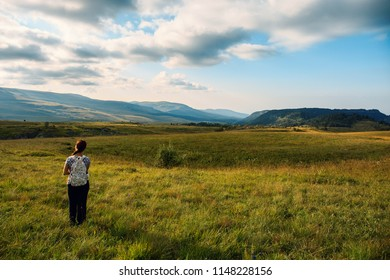 Travel girl in walley at beautiful mountain landscape with blue sky and clouds. Tourist lifestyle concept, travaler with backpack, copy space