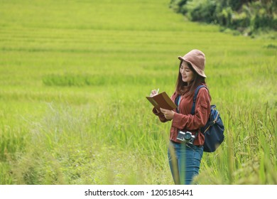 travel guide,Cheerful woman tourist with backpack She is recording a travel note. ,Travel and holidays,