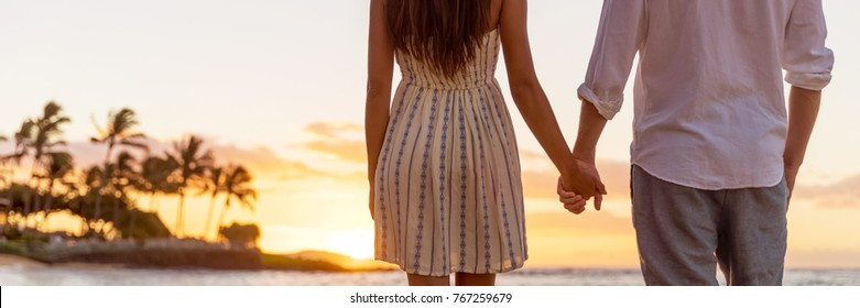 Travel happy honeymoon couple watching sunset on beach holding hands banner