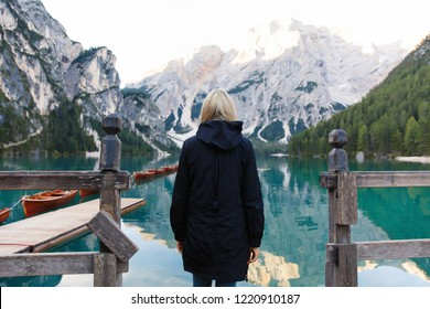 Travel hiker on Lake Braies (Lago di Braies) in Dolomites Mountains, Italy. Hiking travel and adventure.