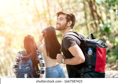 Travel Hiking Man Carrying a Backpack on the back and Walking in National Park. Caucasian man Smiling Happy with Forest in background during Summer Vacation Trip in National Park, Thailand.