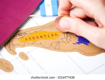 Travel holiday to Argentina concept with passport and flag with female hand choosing Argentina on the map
