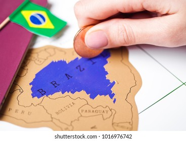 Travel holiday to Brazil concept with passport and flag with female hand choosing Brazil on the map