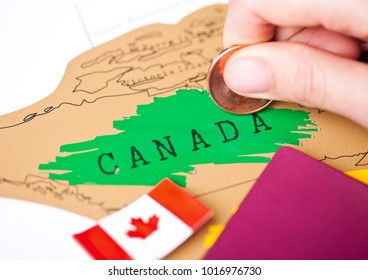 Travel holiday to Canada concept with passport and flag with female hand choosing Canada on the map