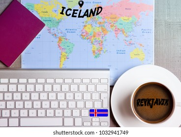 Travel holiday concept with coffee and map with flag on keyboard and passport on wooden table. Travel to Iceland