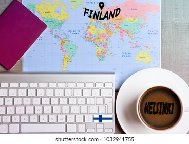 Travel holiday concept with coffee and map with flag on keyboard and passport on wooden table. Travel to Finland Helsinki