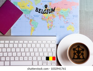 Travel holiday concept with coffee and map with flag on keyboard and passport on wooden table. Travel to Belgium Brussels