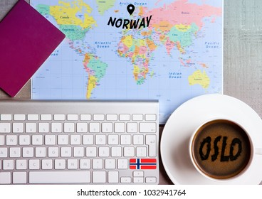Travel holiday concept with coffee and map with flag on keyboard and passport on wooden table. Travel to Oslo Norway