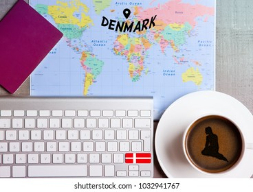 Travel holiday concept with coffee and map with flag on keyboard and passport on wooden table. Travel to Copenhagen Denmark