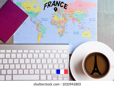 Travel holiday concept with coffee and map with flag on keyboard and passport on wooden table. Travel to Paris France