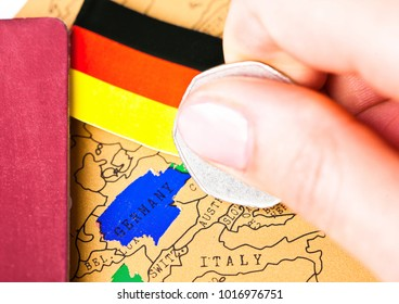 Travel holiday to Germany concept with passport and flag with female hand choosing Germany on the map