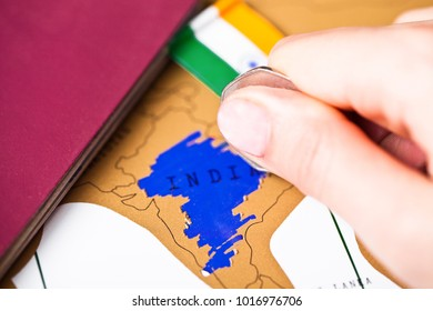 Travel holiday to India concept with passport and flag with female hand choosing India on the map
