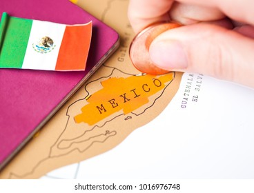 Travel holiday to Mexico concept with passport and flag with female hand choosing Mexico on the map