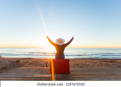 Travel, holiday and people concept - woman tourist sitting near the sea on the red suitcase and in hat and watching sunset and show thumbs up