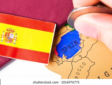Travel holiday to Spain concept with passport and flag with female hand choosing Spain on the map