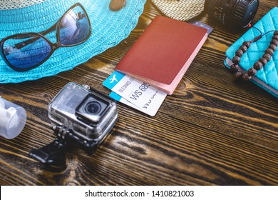 Travel holiday supplies: hat, sunglasses, flip flops, camera passport and airline tickets on old wooden background. The concept of summer going on a trip to the sea. Top view. Flat lay