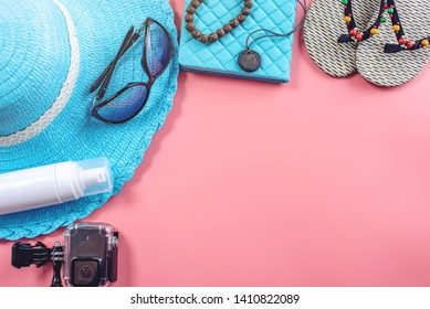 Travel holiday supplies: hat, sunglasses, flip flops, camera passport and airline tickets on pink background. The concept of going on vacation at sea. Top view. Flat lay