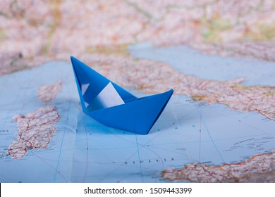 Travel holiday vacation concept origami tourist handmade papercraft paper ship on map near italy close up studion shot