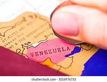 Travel holiday to Venezuela concept with passport and flag with female hand scratching map choosing Venezuela