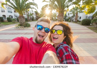Travel, holidays and people concept - Happy married couple taking selfie on vacation