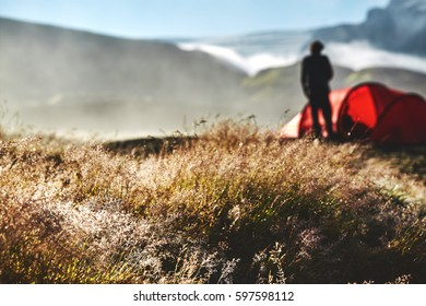 Travel to Iceland. Beautiful Icelandic landscape with mountains, sky and clouds. Trekking in national park Landmannalaugar. foggy morning in Camping . Tents and hikers in the camping. Travel concept.