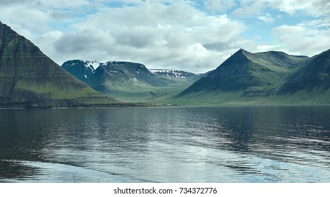Travel to Iceland. beautiful sunrise over the ocean and fjord in Iceland. Icelandic landscape with mountains, sky and clouds. View of fjord near Flateyri, a village in the north-west of Iceland, on