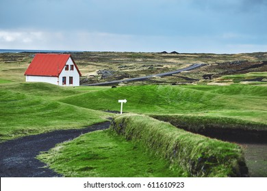 Travel to Iceland. The charming rustic rural house on the mountains background in Icelandic landscape