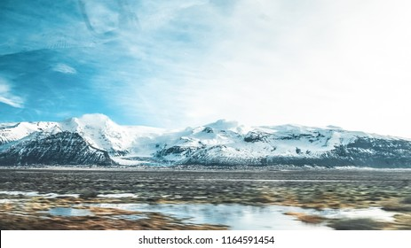 Travel to Iceland. Icelandic landscape with mountains, blue sky on the foreground. View of the road to houses