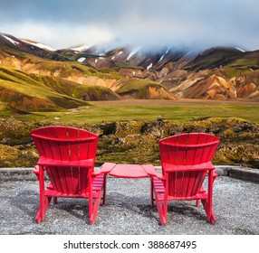 Travel to Iceland in the July. Two red chaise lounges connected by small table stand for tourists. Multi-colored mountains from mineral rhyolite are lit with sun