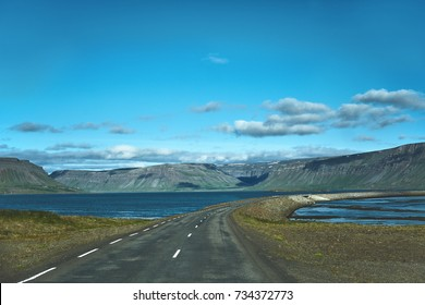 Travel to Iceland. plot of asphalt road in a bright sunny mountain landscape. focus on the road