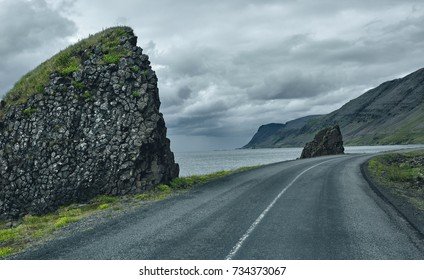 Travel to Iceland. A road along the sea with fog to the town of Isafjordur and a view of the fjord. focus on the road