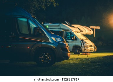 Travel Industry. Modern Camper Vans in the RV Park During Night Hours. Rving Theme.