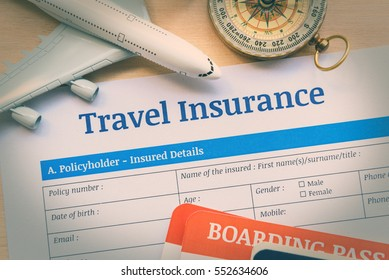 Travel insurance application form on a wood table with a white model airplane, boarding pass and a compass. Travel insurance is intended to cover medical expenses, trip cancellation, lost luggage, etc