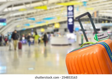 Travel Insurance. Blue suitcase with label at airport.