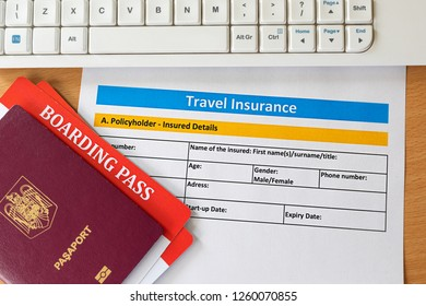 Travel insurance form with boarding pass tickets and passport on wooden table. Agencies sell airplane tickets or travel packages and allow consumers to purchase travel insurance as added service.