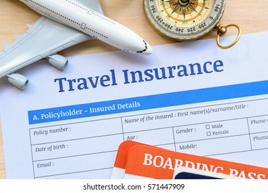 Travel insurance form put on a wood table. Many agent sells airplane tickets or travel packages allow consumers to purchase travel insurance also known as travelers insurance as an added service.
