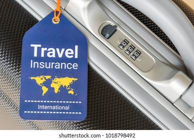 Travel insurance and travel security concept : Top view of travel insurance tag tied on a black suitcase holder near a numeric combination lock. Travel insurance is intended to cover lost luggage.