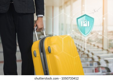 Travel Insurance, Shield protection Travel on virtual screen against Businessman and suitcase in the airport on backdrop, Concept of insurance, Online insurance digital technology.